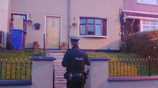 A police offer outside the Bradley home in Creggan,