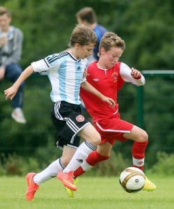 Under-12 action - Maiden City Academy's Josh Kee in a battle for possession with  Hearts' Joseph Evendon. Photo Lorcan Doherty Photography