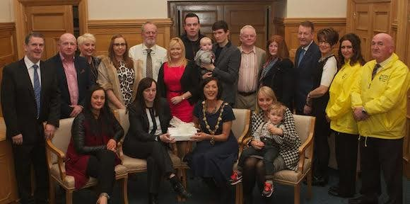 Mayor Brenda Stevenson handing over Books of Condolence to Sharon McCrossan. Seated, on left, Christina McCrossan, and, on right, Charlene McCrossan. Also included are family and friends of the late Martin McCrossan, staff from City Tours. (Photo - Tom Heaney, nwpresspics).